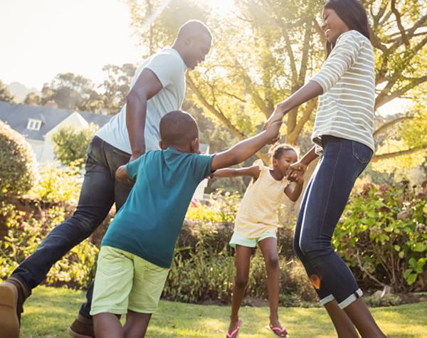 family playing in yard holding hands in a circle